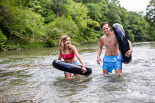 Young Couple Walking Down River With Tubes