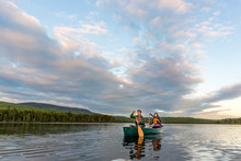 A Young Couple Paddles A Canoe On Long Pond In Maine's North Woods Near Greenville, Maine