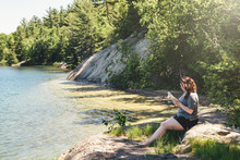 A Young Woman Is Calmly Reading On The Shore Of George Lake On A Bright Summer Day