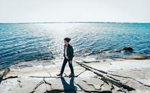 Boy Walking Along Rocky Lake S...