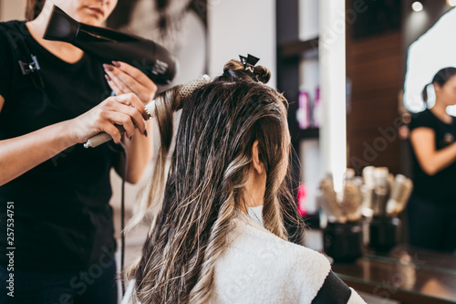 Fotomural Beautiful brunette woman with long hair at the beauty salon getting a hair blowing