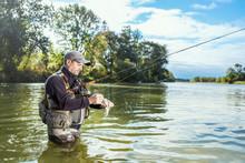 Fisherman Holding Fish, Hamilton, Ontario, Canada