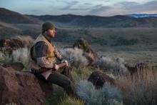 Chukar Hunter Sitting On Rock,...
