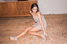 Laughing Young Man Wearing Silver High Heels And Evening Dress Sitting On The Floor In Between Confetti