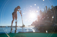 A Woman Stand-up Paddle Boarding In Lake Tahoe, California.