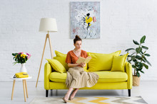Elegant Woman Sitting In Living Room And Reading Book