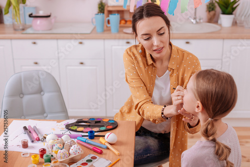 Fotografie, Obraz  Concentrated brunette woman painting face of her kid