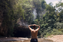 Man Stands In A River Outside A Cave