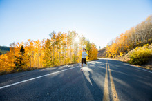 Woman Running On Country Road At Autumn Morning