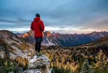 A Climber Stands On A Rock Outcrop Overlooking The Pasayten Wilderness And The North Cascades Of Washington At Sunset.