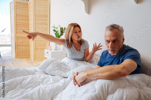 Emotional woman yelling at her husband after betrayal Canvas Print