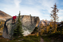 A Young Man Climbs On A Rock Alongside The Colorful Larch Trees And Steep Mountains Of The Cascades In The Pasayten Wilderness In Washington.