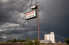 With Angry Clouds Building Over A Grain Silo A Rainbow And Beer Sign Offer Hope.