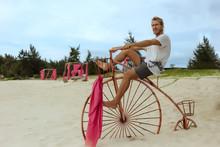 Man Sitting On High Wheel Bicycle On Beach