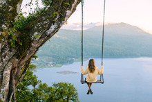 Woman Sitting On Swing Against...