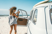 Beautiful Female Surfer Standing Next To Her Vintage Car On The Beach