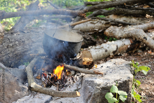 boiling pot above the fire, tourist meal cooking on fire, hot tea on fire Wallpaper Mural