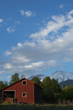 A Red Barn In Front Of A Mount...