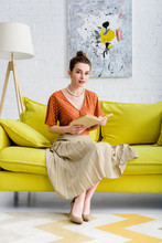 Attractive Elegant Young Woman Holding Book And Looking At Camera While Sitting On Sofa