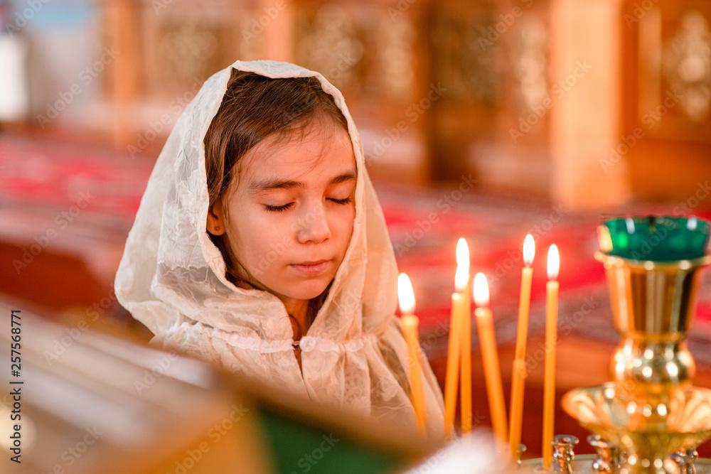 Fototapety, obrazy: Little girl prays in church with eye closed