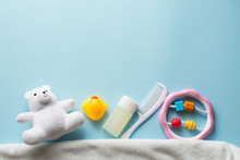 Baby Bath Products Flat Lay. Children Cosmetics Set: Rubber Duck, Towel, Shampoo, Soap, Scissors, Hair Brush Isolated On Blue Background Top View. Web Banner