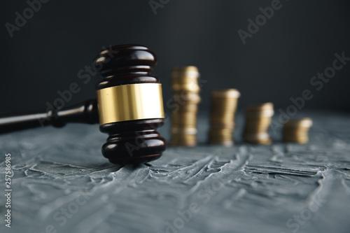 Fotografering  Judge's Hand Holding Gavel Over Stacked Golden Coins
