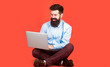 canvas print picture - Happy young man sitting on the floor with and using laptop computer on red background. Holding laptop computer.Young businessman using his laptop, pc. Smiling handsome bearded man worker laptop.