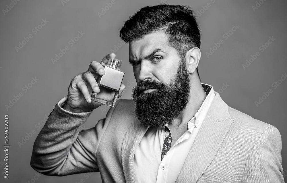 Fototapety, obrazy: Man perfume, fragrance. Masculine perfume. Male fragrance and perfumery, cosmetics. Bearded man holding up bottle of perfume. Fashion cologne bottle. Bearded male prefers expensive fragrance smell.