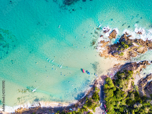 Foto The Pass at Byron Bay from an aerial view with surfers and blue water
