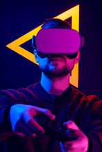 Man Wearing Virtual Reality Goggles Interacting With VR Using Game Pad Wireless Controller. VR Headset Videogame In 80's Synth Wave And Retrowave Glowing Triangle Futuristic Aesthetics.