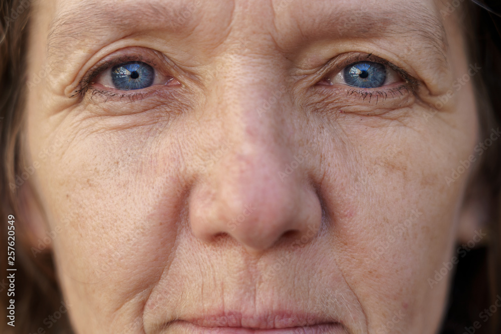 Fototapeta Cropped face of a blue-eyed middle-aged woman