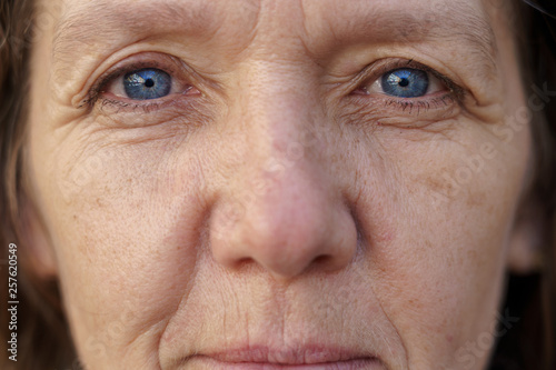 Obraz Cropped face of a blue-eyed middle-aged woman - fototapety do salonu