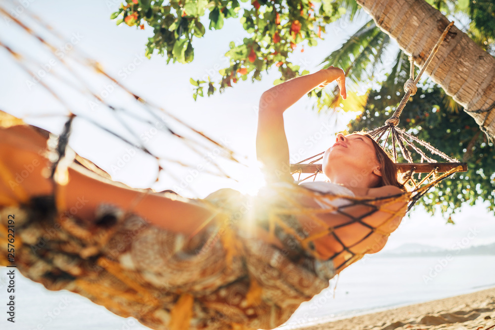 Fototapeta Careless blonde longhaired woman relaxing in hammock hinged between palm trees and playing with sun rays