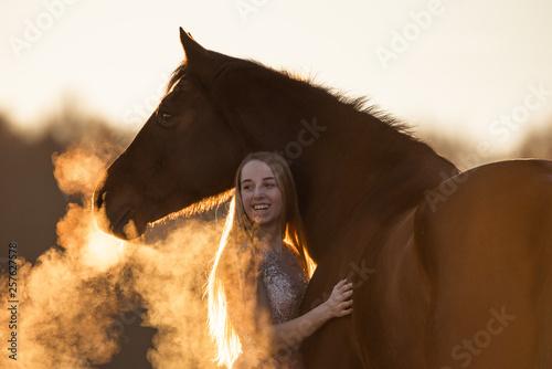 Obraz na plátně  Frau und Pferd schauen im Sonnenaufgang in die gleiche Richtung