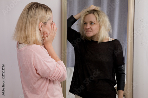Photo  girl looks at herself in the mirror, sees himself in another reflection