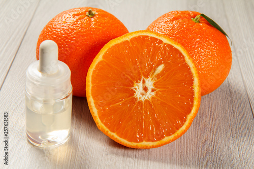 Cut orange with two whole oranges and bottle with aromatherapy oil on wooden boards.