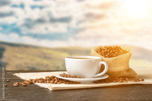 Photo sur Toile Café en grains Cup of hot coffee with beans on background