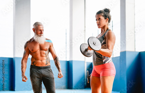 Fit woman making curl biceps exercise with dumbbells in fitness gym center - Female athlete training with her personal trainer inside wellness sport club - Workout and bodybuilding lifestyle concept