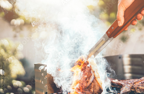 Fotomural Man chef grilling beef steak at barbecue dinner party outdoor - Close up male ha