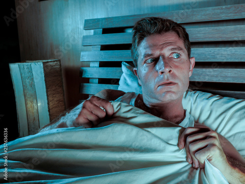 Fotomural  sleepless young man lying in bed stressed and scared suffering nightmare and hor
