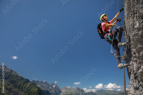 Slika na platnu Pretty, female climber on a via ferrata - climbing on a rock in Swiss Alps