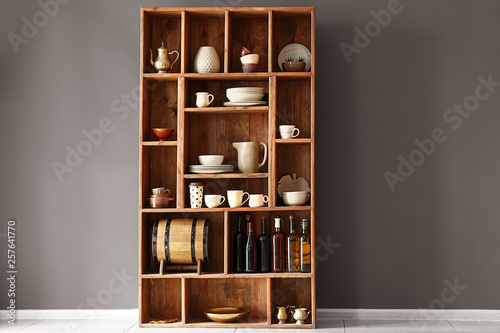 Open cupboard with clean dishes near color wall in kitchen Canvas Print