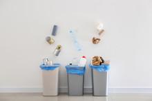 Garbage Falling Into Trash Bins Near White Wall