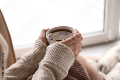 Obraz Young woman drinking hot tea at home, closeup - fototapety do salonu