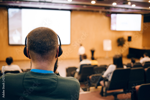 Fotografía  Business man is listen seminar at conference using headphones  for translation
