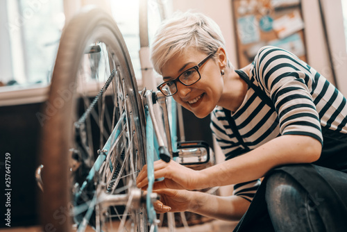 Beautiful Caucasian female worker with short blonde hair and eyeglasses crouching and repairing bicycle. Bike workshop interior.