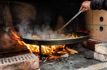 Cooking And Making A Traditional Spanish Paella Over Open Fire.
