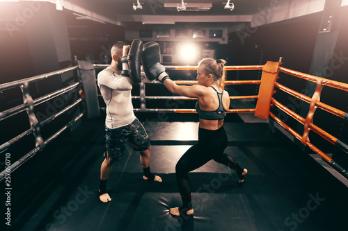 Fotomural  Strong muscular boxer Caucasian woman kicking and having training in ring