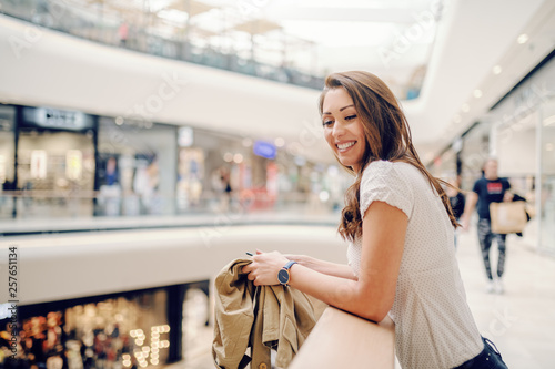 Fotografía  Smiling Caucasian charming brunette leaning on railing at shopping mall and looking away