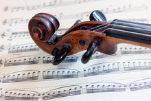 Оld Violin Head On The Background Of Sheet Music. Close Up View.